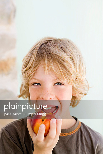 A boy eating a nectarine - p4297468f by Jurgen Magg