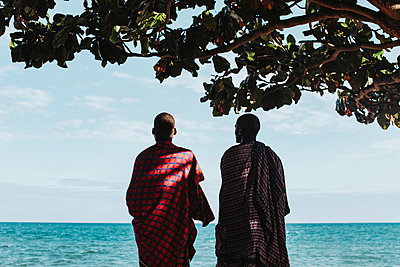Two masai men in traditional clothes standing under big mkungu tree - p1166m2157028 by Cavan Images