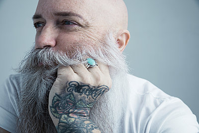 Close up portrait male Caucasian hipster with gray beard and tattooed hand on chin looking away - p1192m1213127 by Hero Images