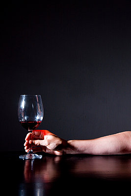 Hand holding an almost empty glass of wine - p1231m1043156 by Iris Loonen
