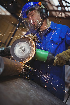 Man cutting metal with circular saw - p1315m1167662 by Wavebreak
