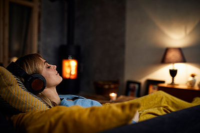 Smiling woman listening music with headphones on couch at home in the evening - p300m1535538 by Rainer Berg