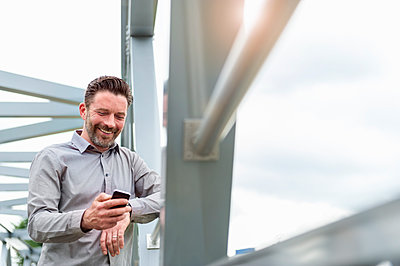Smiling handsome businessman using smart phone while standing on footbridge in city - p300m2188377 by Daniel Ingold