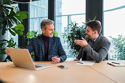 Smiling male professionals with laptop and papers in meeting at board room at work place - p300m2273941 by Daniel Ingold