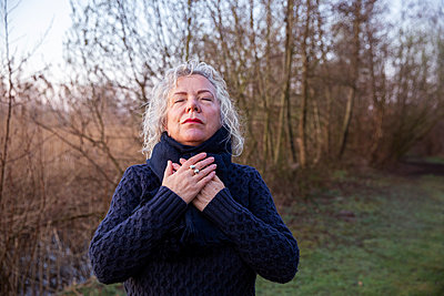 Senior woman with eyes closed praying in front of bare tree - p300m2293463 by Frank van Delft