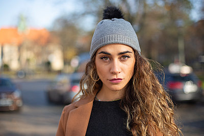 Young woman with bobble cap outdoors - p975m2222103 by Hayden Verry