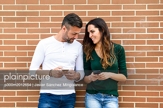 Couple looking at their smartphones at a brick wall - p300m2012654 von Javier Sánchez Mingorance