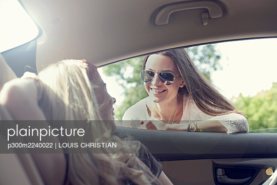 Young woman leaning on car window while talking to friend during road trip - p300m2240022 by LOUIS CHRISTIAN