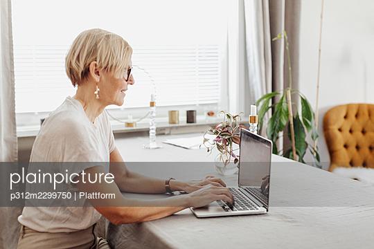 Smiling woman using laptop at home - p312m2299750 by Plattform