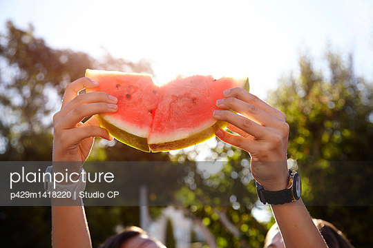 Teenage girls holding up watermelon in street - p429m1418220 by Studio CP