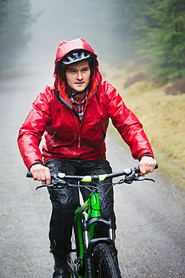 Man mountain biking in rain - p1023m2135863 by Robert Daly