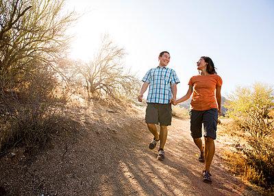 Happy couple walking on dirt road against clear sky - p1166m1534577 by Cavan Social