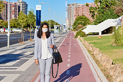 Woman walking down the street with a mask. - p1166m2218306 by Cavan Images
