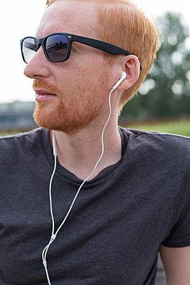 Rothaariger Mann mit Kopfhörer. - p1396m1464950 von Hartmann + Beese