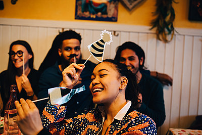 Cheerful young woman holding props while sitting against multi-ethnic friends at restaurant during dinner party - p426m2046281 by Maskot