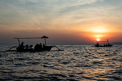 Indonesian jukung, traditional wooden outrigger canoe at sunrise; Lalang, Bali, Indonesia - p442m2155027 by Peter Langer