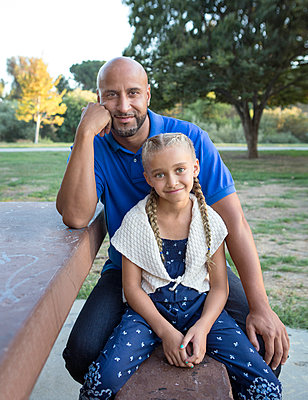 Father and daughter smiling on picnic table in park - p555m1411712 by Sam Diephuis