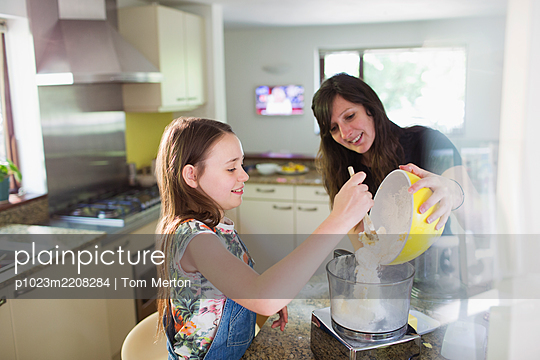 Mother and daughter baking in kitchen - p1023m2208284 by Tom Merton