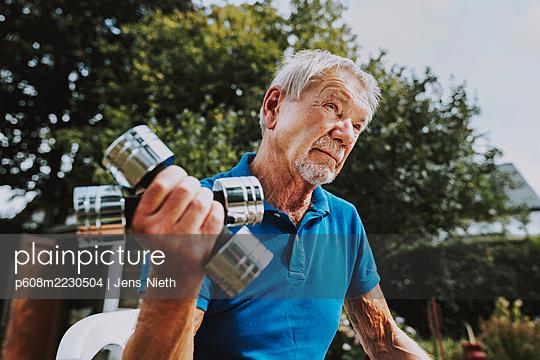 Elderly man doing dumbbell training - p608m2230504 by Jens Nieth