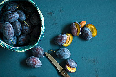 Sliced and whole plums and a kitchen knife - p300m2028738 by Achim Sass