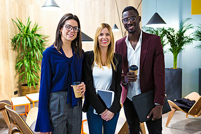 Business people standing in hotel lobby, smiling - p300m2083463 by Josep Suria