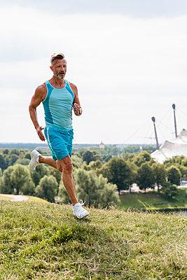 Sporty man jogging in a park - p300m2119169 von Daniel Ingold