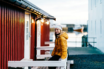 Portrait of smiling tourist on a porch at Hamnoy, Lofoten, Norway - p300m2166475 by Daniel González