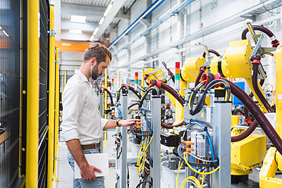 Young male engineer looking at machinery's robotic arm in automated factory - p300m2197475 by Daniel Ingold