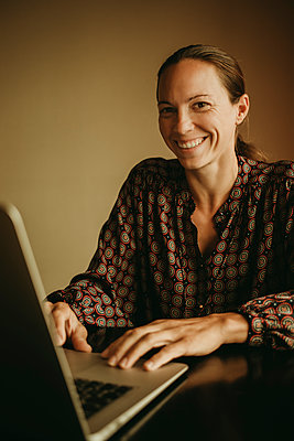 Smiling businesswoman working on laptop while sitting in office - p300m2220705 by David Molina Grande