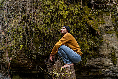 Thoughtful male hiker crouching on tree stump in forest - p300m2273560 by VITTA GALLERY