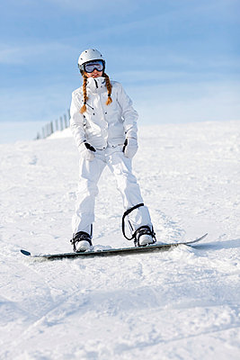 Teenage girl snowboarding - p312m742625f by Ulf Huett Nilsson