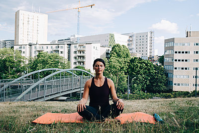 Young woman meditating on field against buildings in city - p426m2036905 by Maskot