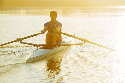 Caucasian man rowing on river at sunset - p555m1303396 by Pete Saloutos