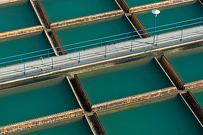 Aerial view of walkway over water treatment tanks - p555m1411695 by Spaces Images