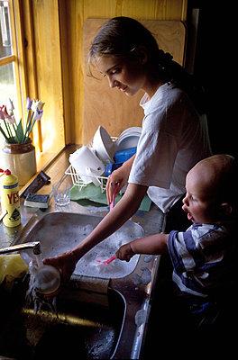 Mother with son washing utensils - p8476199 by Bengt Af Geijerstam