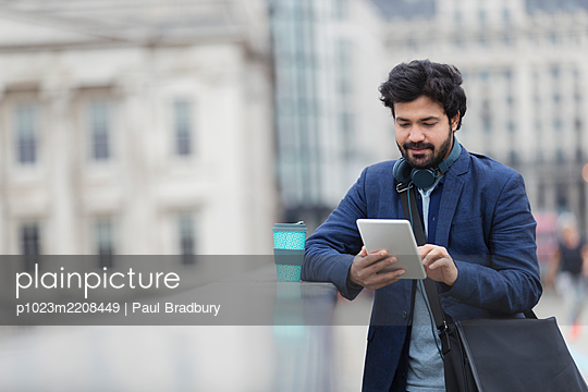 Businessman using digital tablet on city bridge - p1023m2208449 by Paul Bradbury