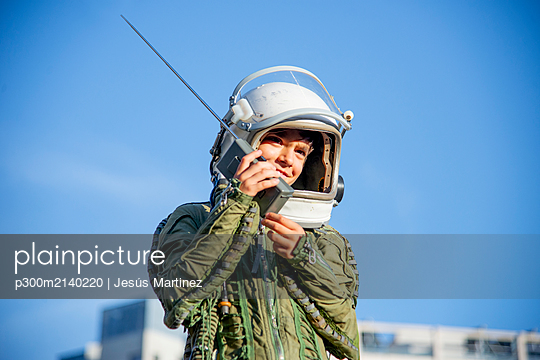 Boy wearing a space suit and using walkie talkie - p300m2140220 by Jesús Martinez
