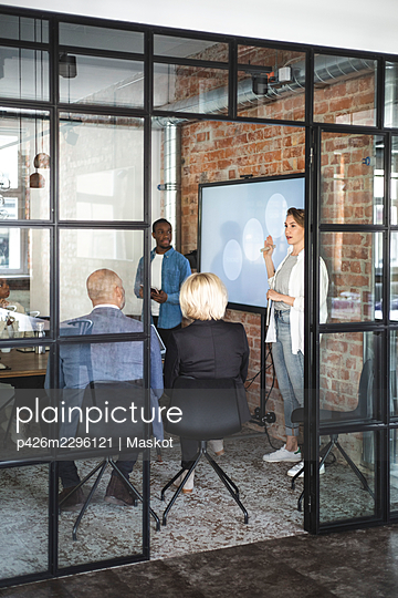 Female computer programmer giving presentation to advisors seen through doorway of startup company - p426m2296121 by Maskot