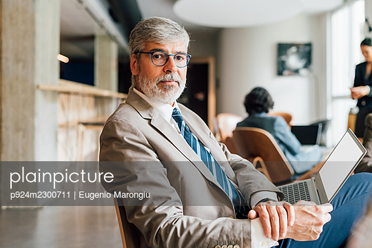 Italy, Portrait of businessman with laptop in creative studio - p924m2300711 by Eugenio Marongiu