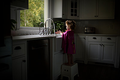 Side view of girl wearing pink cape washing hands in kitchen sink while standing on stool at home - p1166m2067536 by Cavan Images