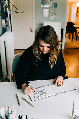 Stock photo of a lettering artist at work with her sketch book. - p1166m2162670 by Cavan Images