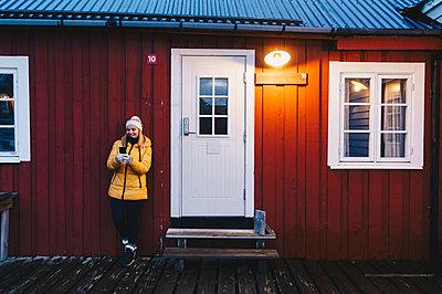 Tourist using smartphone at a hut in Hamnoy, Lofoten, Norway - p300m2166315 by Daniel González