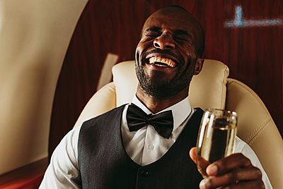 Young male entrepreneur laughing while holding champagne in private jet - p300m2257070 by OneInchPunch