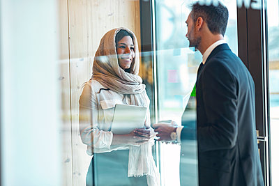 Smiling businesswoman with businessman at entrance of office - p300m2282121 by Josep Suria