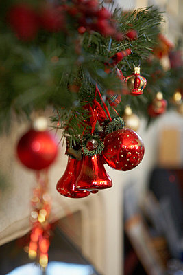 Red baubles and bells on Christmas tree - p349m789715 by Brent Darby