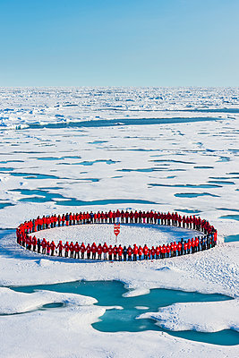 People wearing red forming circle around North Pole, Arctic - p871m2077691 by Michael Runkel