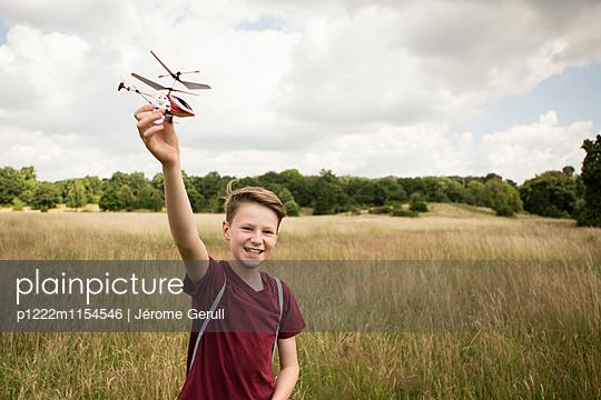 Junge mit Spielzeughubschrauber - p1222m1154546 von Jérome Gerull