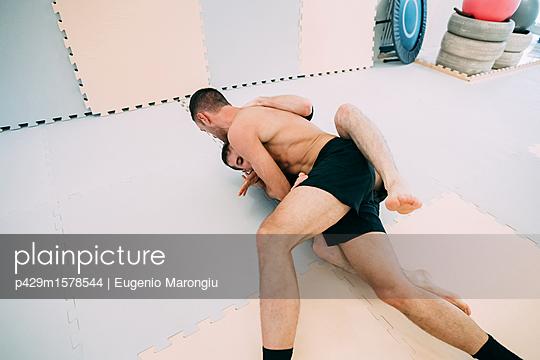 plainpicture - plainpicture p429m1578544 - Men on floor in gym wrestling - plainpicture/Cultura/Eugenio Marongiu