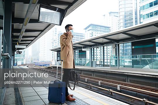 UK, London, Man waiting at train station platform - p924m2271290 by Peter Muller