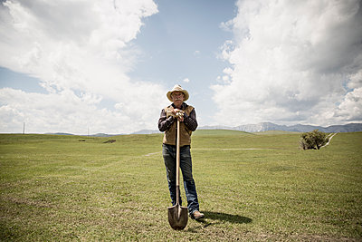 Portrait confident rancher with shove in rural field - p1192m1063878f by Hero Images